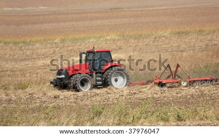 Red farm tractor discing a farm field after harvest