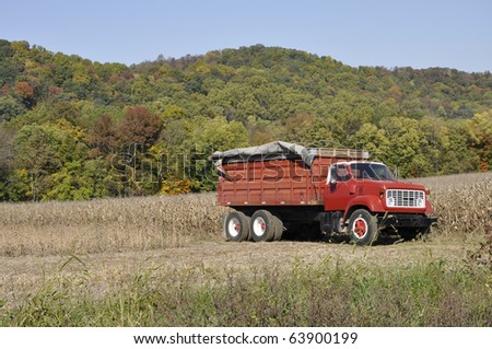 Red farm truck by a field of cut down corn. - stock photo