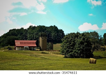 Red Farmhouse Nestled Above Green Field - stock photo