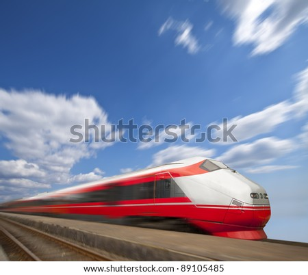 Red fast train on blue sky background passing by - stock photo