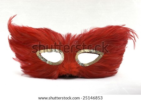 Red feather mask for halloween or a masquerade ball - stock photo