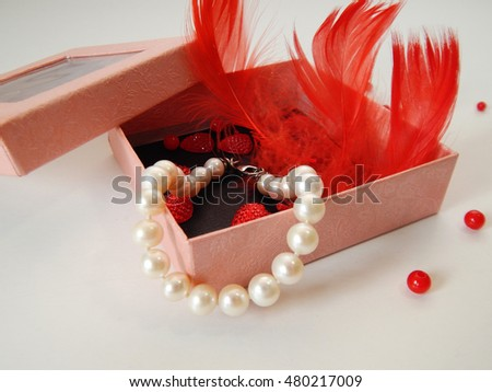 red feathers and pearls in a box