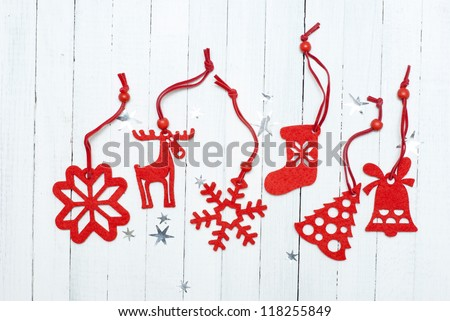 red felt christmas ornaments on white wooden table background - stock photo