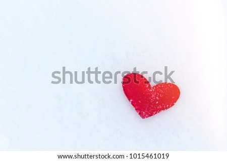 red felt heart figure on snow, winter day with sun glare