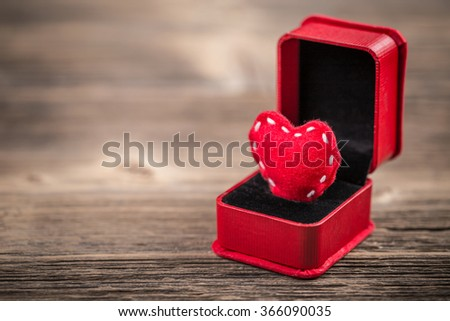 Red felt heart in ring box on wooden background - stock photo