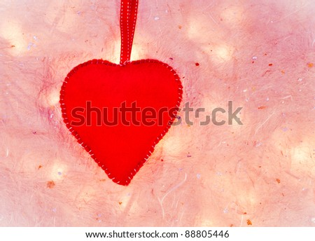 Red felt heart on a textured pale background - stock photo