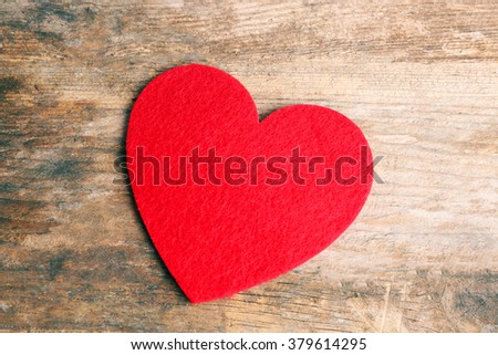Red felt heart on wooden background - stock photo