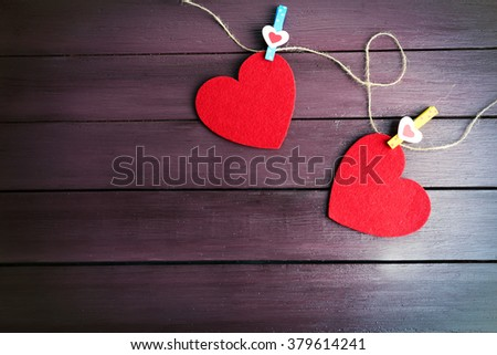 Red felt hearts are on cord against purple wooden background - stock photo