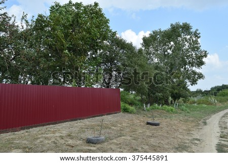 Red fence of metal sheets on a background of green trees. Fence in the country. - stock photo