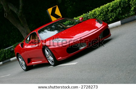 Red Ferrari F430 on the road in Singapore - stock photo