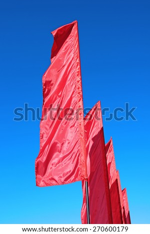 Red festive flags during a holiday against the blue sky - stock photo