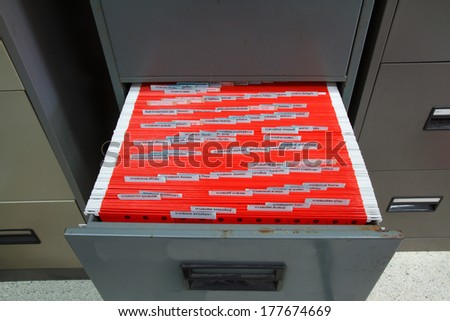 Red filing in the drawer of the filing cabinet. - stock photo