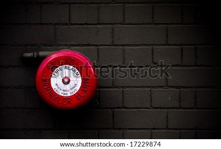 red fire alarm bell set against dark grey brick wall - stock photo