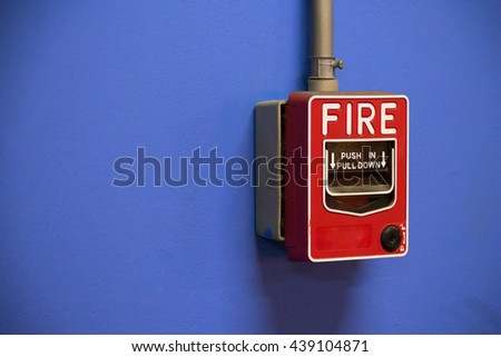 red fire alarm box on purple wall in underground floor