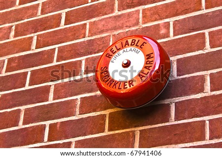 Red fire alarm on brick wall - stock photo