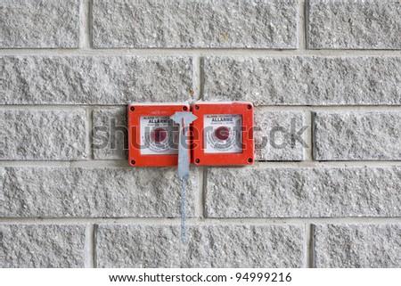 red fire alarm on gray brick wall - stock photo