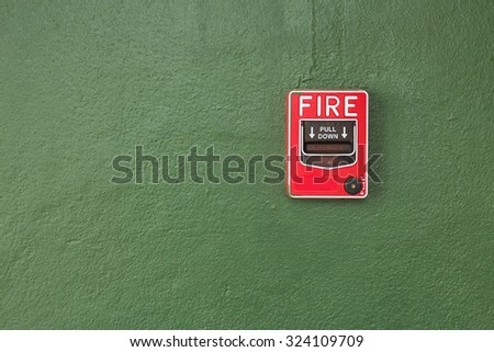 Red fire alarm switch on grunge green background.