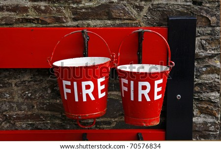 Red fire buckets at an old railway station - stock photo