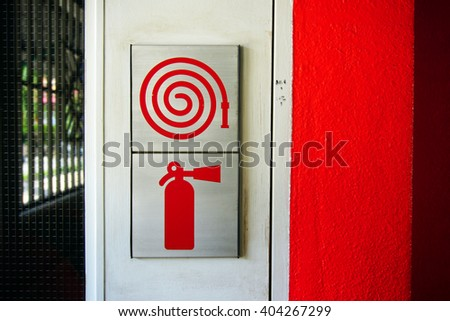 red fire hose and fire extinguisher signs - stock photo