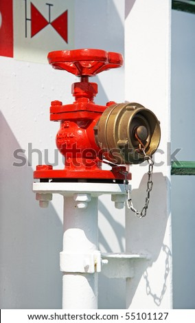 Red fire hydrant on a white pipe with a copper cover - stock photo