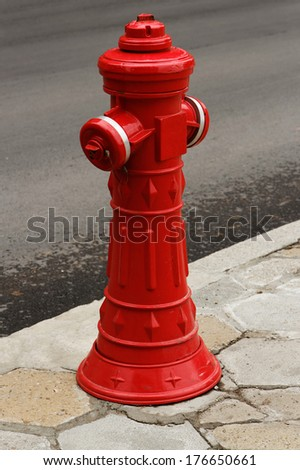 Red fire hydrant on the street - stock photo