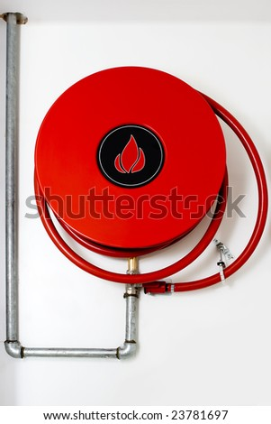Red fire hydrant reel on a wall waiting for action - stock photo