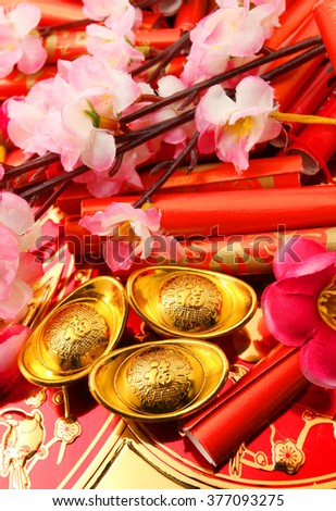 "Red firecrackers,Shoe-shaped gold ingot (Yuan Bao with Chinese character ""Fu"" means fortune) and Plum Flowers - best for Chinese New Year use - stock photo"