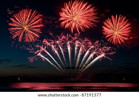 red firework explosions above the sea - stock photo