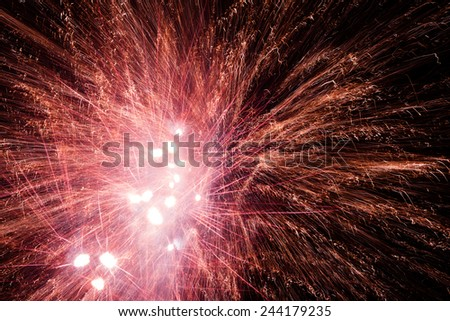 Red fireworks explosions in the night sky - stock photo