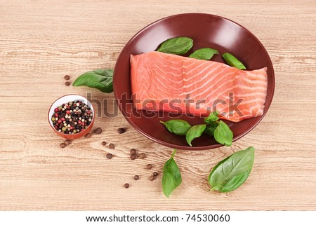 Red fish on the plate with pepper and green leaves - stock photo