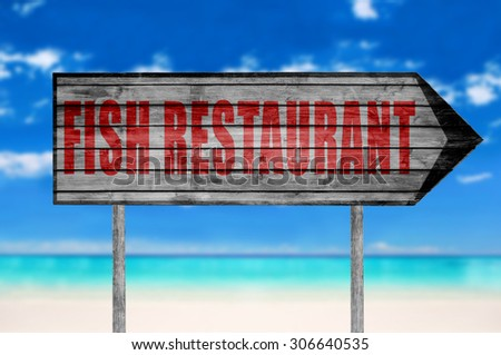 Red Fish Restaurant wooden sign with on a beach background - stock photo