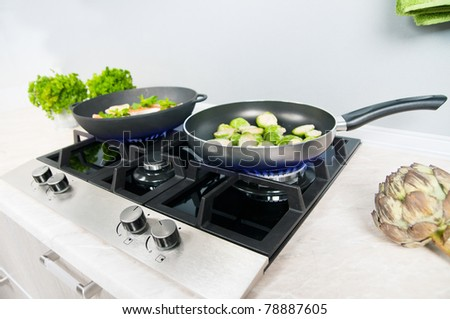 Red fish with mint and lemon prepared in a black skillet in the kitchen - stock photo