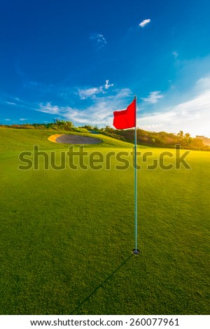 Red flag and sand bunker at the beautiful golf course at sunset, sunrise time. Vertical. - stock photo