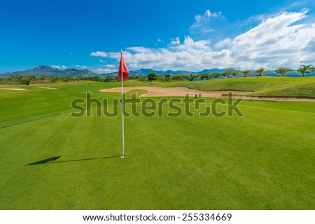 Red flag and sand bunkers at the gorgeous golf course of the luxury Mexican resort. - stock photo