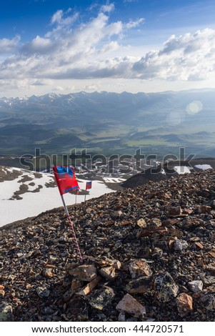 red flag flying in the background of the mountains - stock photo