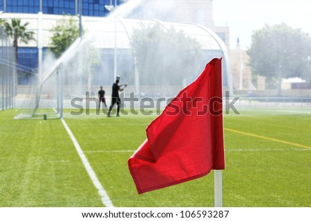 Red flag in corner of soccer field in summer day.
