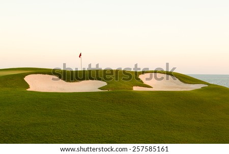 Red flag of golf hole above sand trap or bunker on beautiful ocean front course at sunset - stock photo