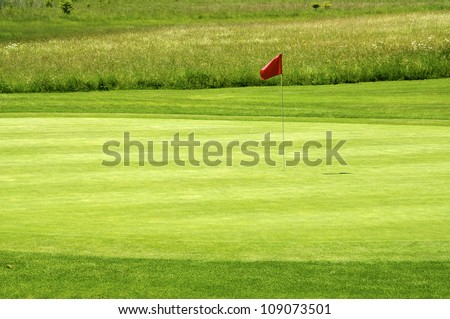 Red flag on a beautiful golf course - stock photo