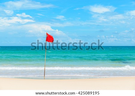 Red flag on tropical beach and azure sea - stock photo