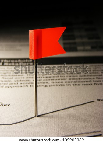 Red flag pin in graph on paper - stock photo