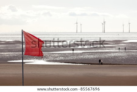 Red flag warns swimmers as wind turbines turn in the ocean off a sandy beach near Liverpool on a cold and cloudy day - stock photo