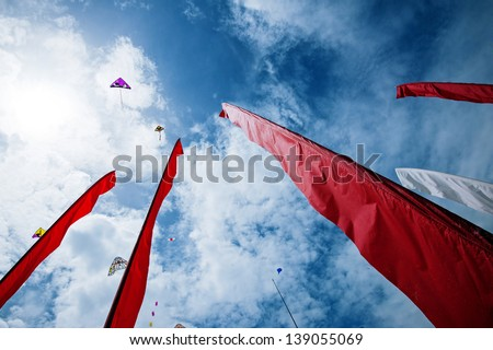 Red flags and kites in the sky. - stock photo