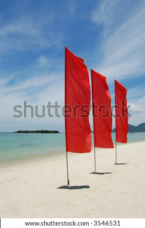 Red flags on white sand beach - stock photo