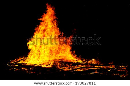 red flames of huge bonfire or campfire as black backgorund - stock photo