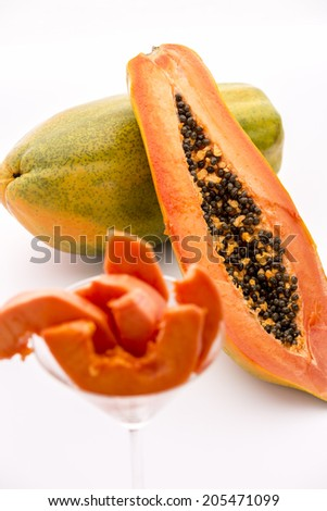 Red-fleshed Papaya.  A longitudinal section across the globose body of a papaya fruit does reveal its red-fleshed pulp and countless black seeds in its central cavity.