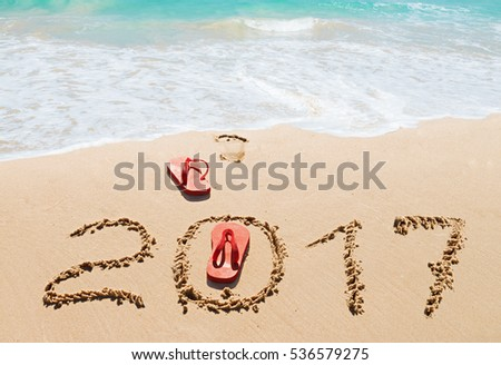 Red flip flops and digits 2017 on the beach sand.Concept of summer vacations, new year  and   Christmas