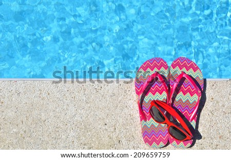 Red flip-flops and sunglasses beside the swimming pool -- Summer vacations concept  - stock photo