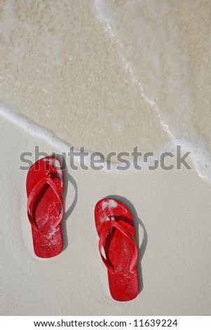 Red Flip flops on a tropical beach with gentle wave - stock photo