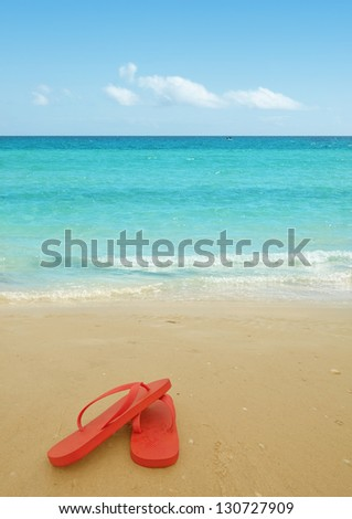 Red flip flops on the beach sand.Concept of summer vacations - stock photo