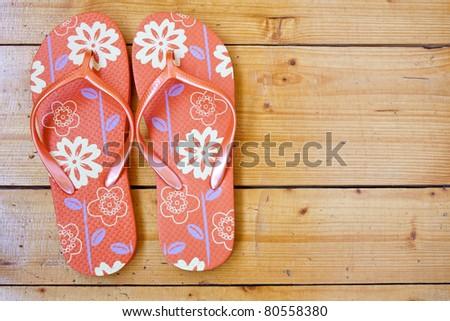 red flip flops on the wooden floor. - stock photo